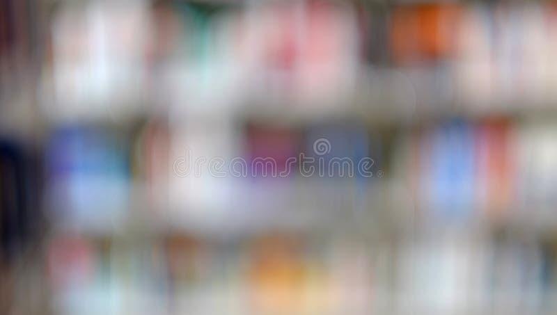 Εικόνα θαμπάδων του ραφιού με τα βιβλία στη βιβλιοθήκη r στοκ εικόνα