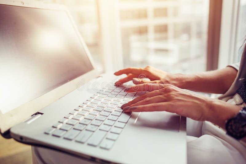 Εικόνα κινηματογραφήσεων σε πρώτο πλάνο της θηλυκής γυναίκας χεριών που εργάζεται στο lap-top στην αρχή στοκ εικόνες
