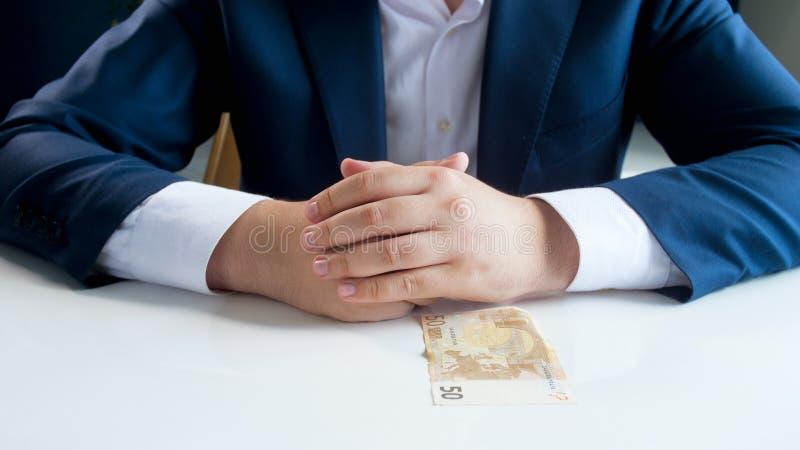Εικόνα κινηματογραφήσεων σε πρώτο πλάνο της συνεδρίασης επιχειρηματιών πίσω από το γραφείο και της εξέτασης το ευρο- τραπεζογραμμ στοκ εικόνα