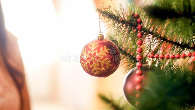 Εικόνα κινηματογραφήσεων σε πρώτο πλάνο της όμορφης κόκκινης ένωσης μπιχλιμπιδιών στον κλάδο χριστουγεννιάτικων δέντρων στοκ φωτογραφία