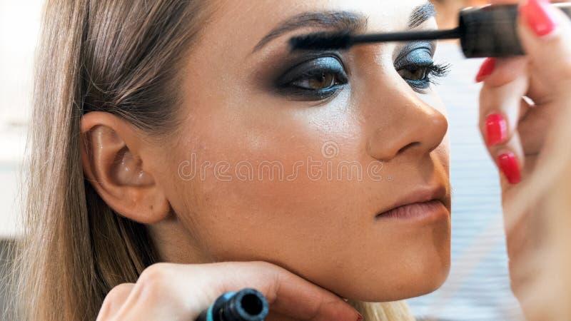 Εικόνα κινηματογραφήσεων σε πρώτο πλάνο του καλλιτέχνη Makeup που χρωματίζει τα νέα πρότυπα μάτια ` s με μαύρο mascara στοκ φωτογραφία