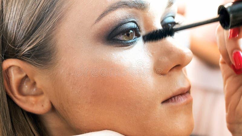 Εικόνα κινηματογραφήσεων σε πρώτο πλάνο του καλλιτέχνη makeup που εφαρμόζει τα μάτια smokey makeup στοκ εικόνα με δικαίωμα ελεύθερης χρήσης