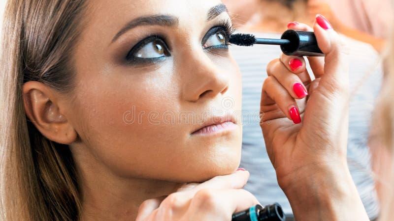 Εικόνα κινηματογραφήσεων σε πρώτο πλάνο του καλλιτέχνη profesinal makeup που χρωματίζει πρότυπο ` s eyelashes με mascara στοκ εικόνα