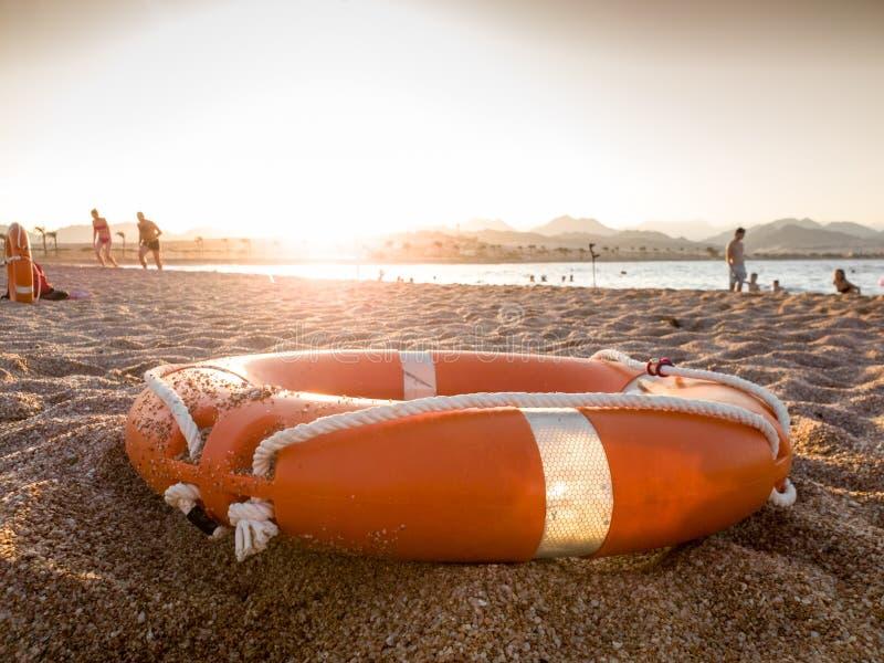 Εικόνα κινηματογραφήσεων σε πρώτο πλάνο του κόκκινου πλαστικού δαχτυλιδιού αποταμίευσης ζωής στην αμμώδη παραλία θάλασσας στο φως στοκ εικόνες