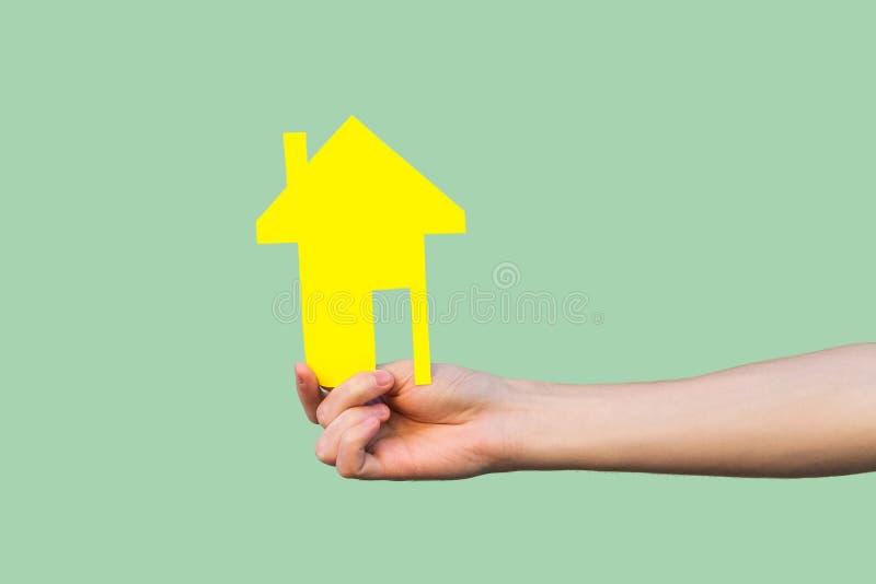 Εικόνα κινηματογραφήσεων σε πρώτο πλάνο των χεριών που παρουσιάζουν, που κρατά το κίτρινο μικρό σπίτι εγγράφου, έννοια υποθηκών,  στοκ φωτογραφία