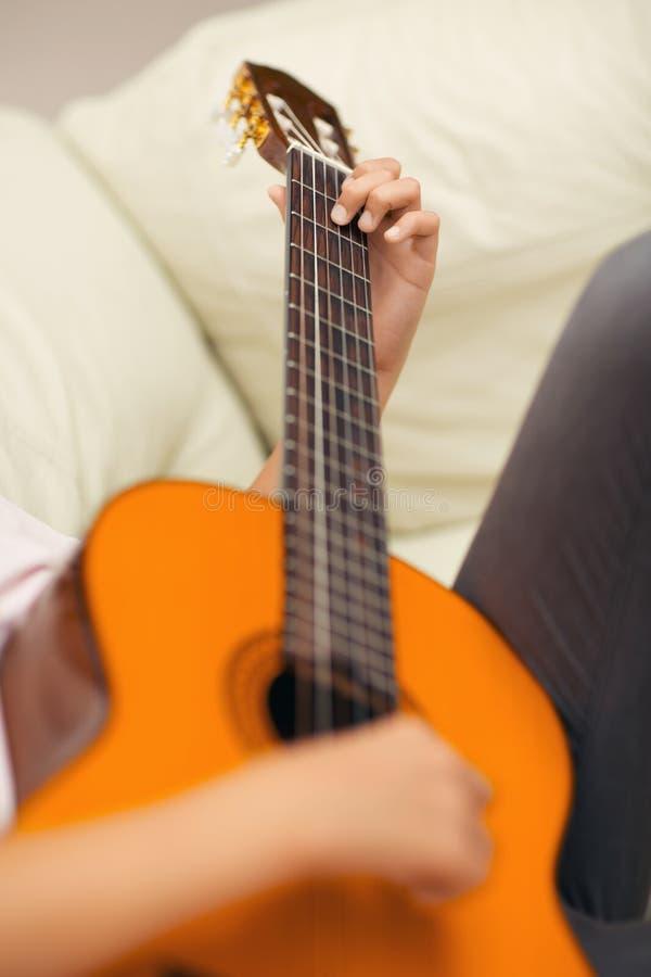 Εικόνα κινηματογραφήσεων σε πρώτο πλάνο της κιθάρας στην καυκάσια γυναίκα στοκ εικόνες