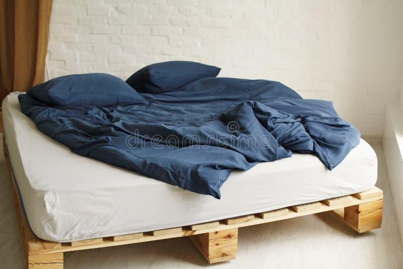 Εικόνα ξύλινου κρεβατιού με μπλε πανί κρεβατιού σε φωτεινή κρεβατοκάμαρα στοκ εικόνα