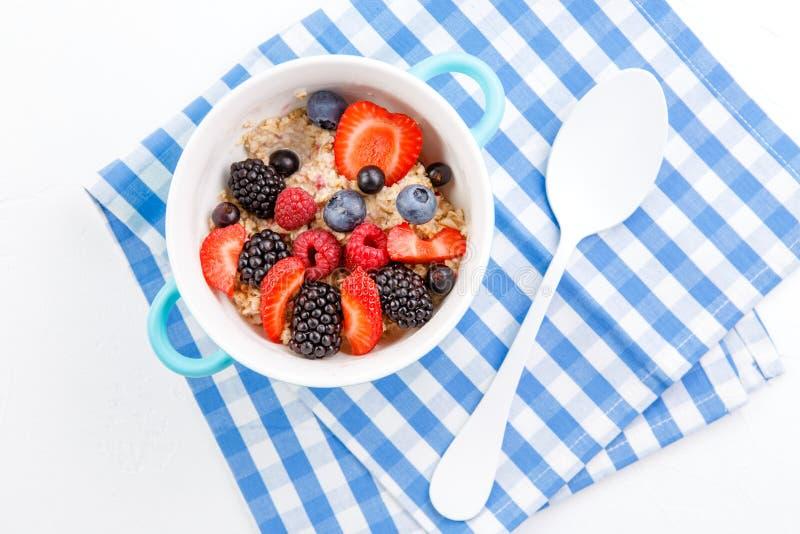 Εικόνα πάνω από oatmeal με τα σμέουρα, φράουλες, βατόμουρα στον πίνακα στοκ εικόνες