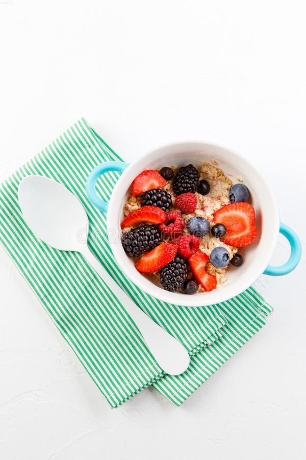 Εικόνα πάνω από oatmeal με τα σμέουρα, φράουλες, βατόμουρα στον πίνακα στοκ φωτογραφία