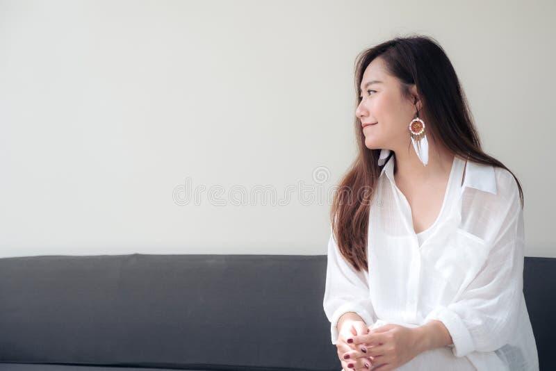 Εικόνα πορτρέτου μιας όμορφης ασιατικής γυναίκας στην άσπρη συνεδρίαση φορεμάτων με το αίσθημα ευτυχής στοκ φωτογραφία