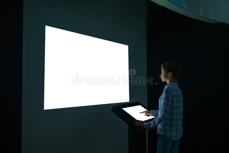 Εικόνα προτύπων - γυναίκα που εξετάζει την άσπρη κενή μεγάλη επίδειξη τοίχων στοκ εικόνα