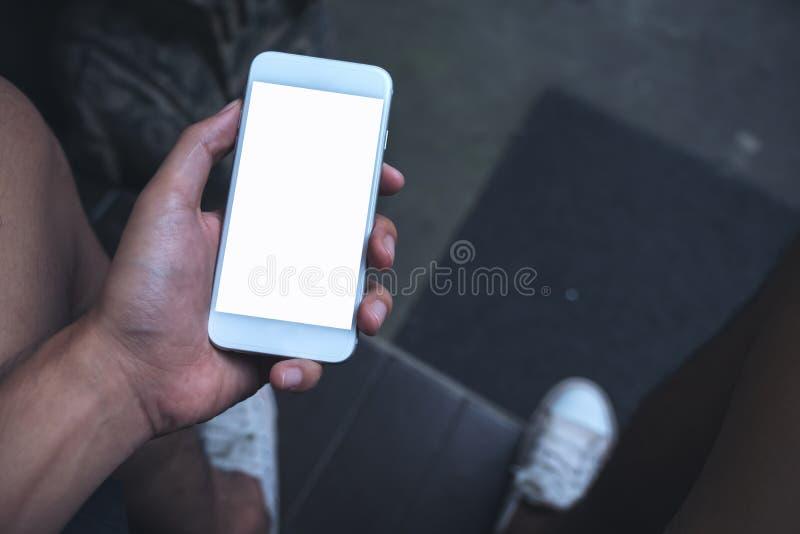 Εικόνα προτύπων ενός χεριού ατόμων ` s που κρατά το άσπρο κινητό τηλέφωνο με την κενή οθόνη στο μηρό στοκ φωτογραφία