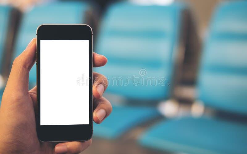 Εικόνα προτύπων ενός χεριού ατόμων ` s που κρατά το μαύρο κινητό τηλέφωνο και την κενή άσπρη οθόνη με τα μπλε καθίσματα στον αερο στοκ εικόνες