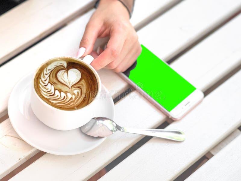 Εικόνα προτύπων του άσπρου κινητού τηλεφώνου με την κενή μαύρη οθόνη και του χεριού που κρατά τον καυτό καφέ latte στον εκλεκτής  στοκ εικόνες