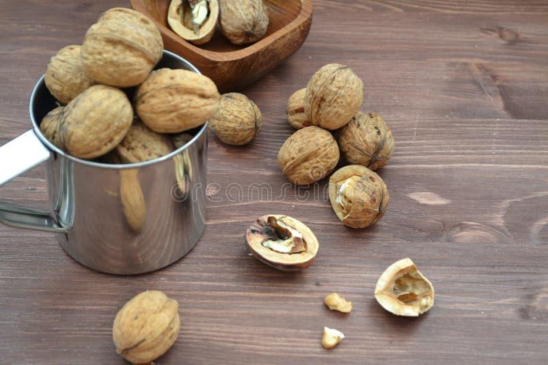 Εικόνα ρουτίνας: καρύδια σε μεταλλική κούπα Ξύλινο φόντο Αντικείμενο μακροεντολής στοκ φωτογραφία με δικαίωμα ελεύθερης χρήσης