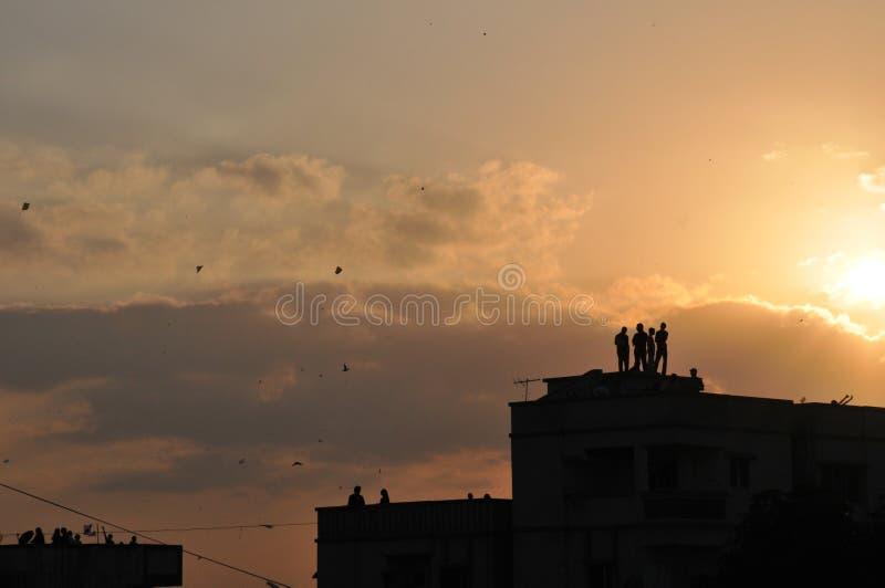 Εικόνα σκιαγραφιών των ανθρώπων που πετούν τους ικτίνους από το πεζούλι σπιτιών στην Ινδία στοκ εικόνα με δικαίωμα ελεύθερης χρήσης