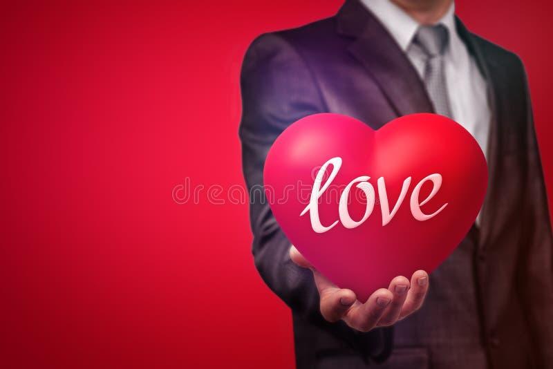 """Εικόνα συγκομιδών του ατόμου στο κοστούμι που κρατά μια μεγάλη κόκκινη καρδιά με τη λέξη """"αγάπη """"στο κόκκινο υπόβαθρο στοκ εικόνα με δικαίωμα ελεύθερης χρήσης"""