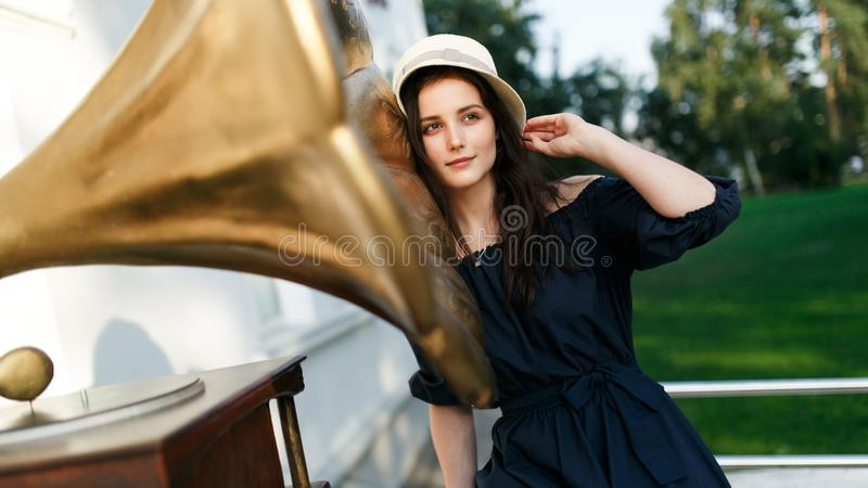 Εικόνα της γυναίκας στο μαύρο φόρεμα και του καπέλου δίπλα gramophone στοκ εικόνα με δικαίωμα ελεύθερης χρήσης