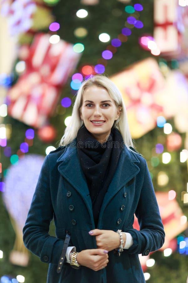 Εικόνα της γυναίκας στο παλτό ενάντια στο χριστουγεννιάτικο δέντρο στο κατάστημα στοκ φωτογραφία με δικαίωμα ελεύθερης χρήσης