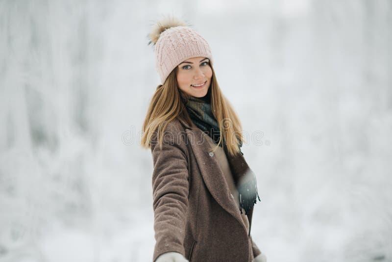 Εικόνα της ευτυχούς ξανθής γυναίκας στο καπέλο στον περίπατο στο χειμερινό δάσος στοκ εικόνες