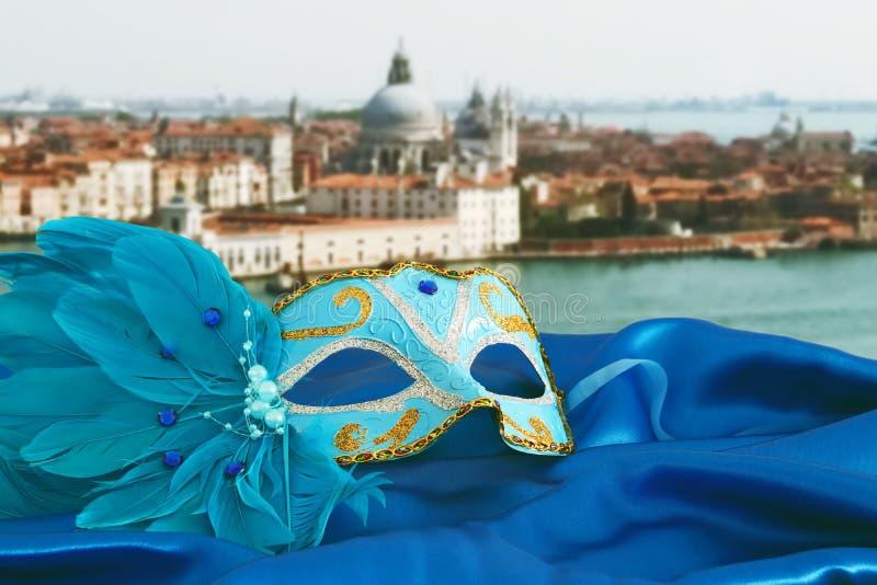 Εικόνα της κομψής ενετικής μάσκας στο ύφασμα μεταξιού μπροστά από το μουτζουρωμένο υπόβαθρο της Βενετίας στοκ φωτογραφίες με δικαίωμα ελεύθερης χρήσης