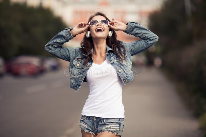 Εικόνα της νέας ευτυχούς γυναίκας, μουσική ακούσματος και κατοχή της διασκέδασης στοκ εικόνες