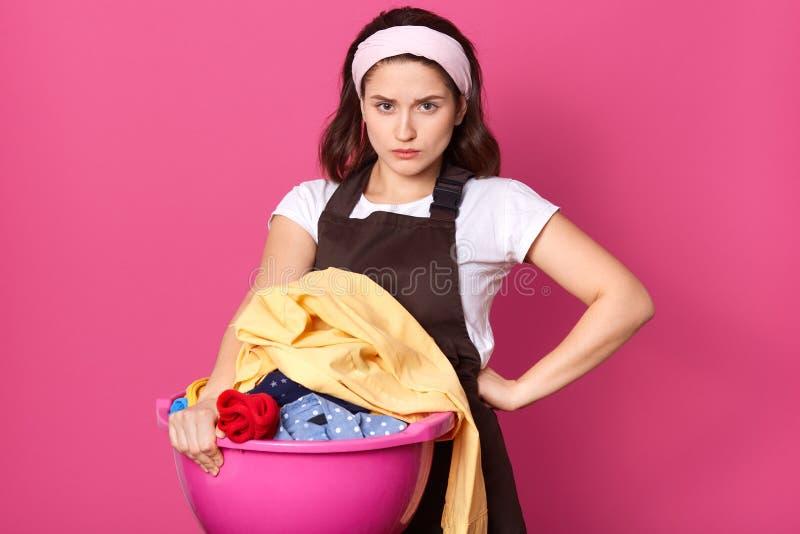 Εικόνα της νέας νοικοκυράς με το συνοφρύωμ πρόσωπο που βάζει ένα χέρι στη μέση, που κρατά το πλυντήριο στη λεκάνη της, που έχει δ στοκ εικόνες