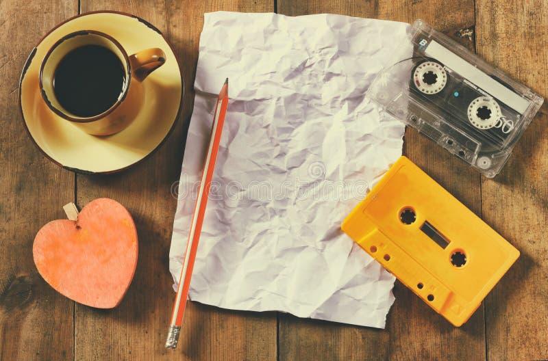 Εικόνα της ταινίας κασετών πέρα από το ξύλινο επιτραπέζιο κενό τσαλακωμένο έγγραφο Τοπ όψη αναδρομικό φίλτρο στοκ εικόνες