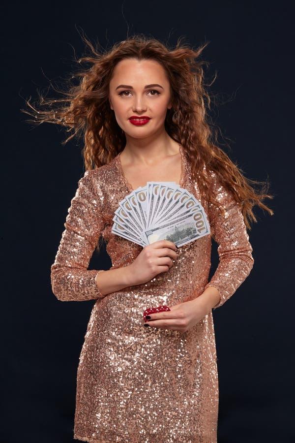 Εικόνα της τυχερής ευτυχούς γυναίκας με καφετή μακρυμάλλη με τον ανεμιστήρα 100 λογαριασμών δολαρίων, μέρη των χρημάτων μετρητών, στοκ εικόνες με δικαίωμα ελεύθερης χρήσης