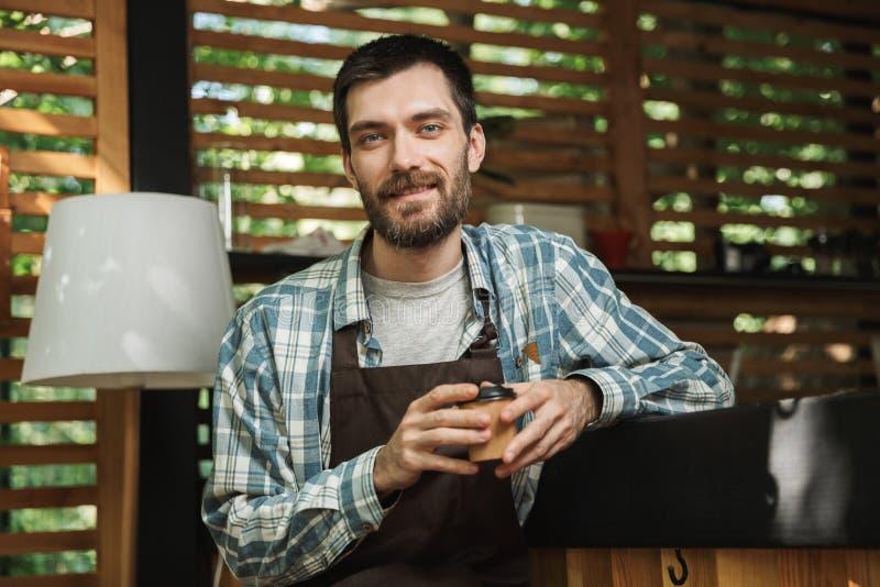 Εικόνα της χαρούμενης συνεδρίασης αγοριών σερβιτόρων στο φραγμό εργαζόμενος στον καφέ ή το καφέ υπαίθριο στοκ φωτογραφία με δικαίωμα ελεύθερης χρήσης