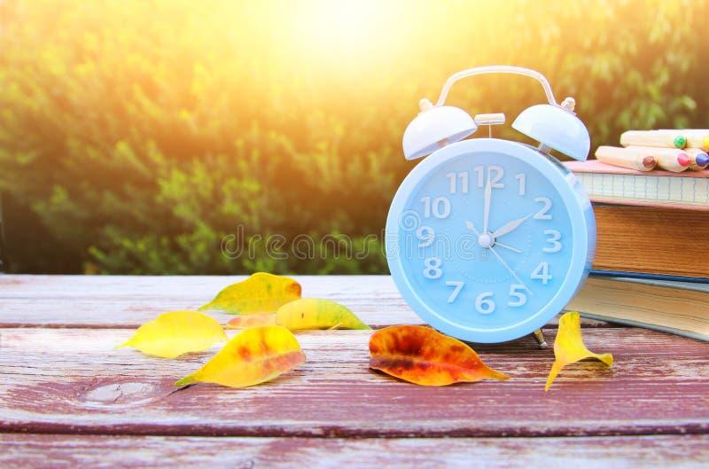 Εικόνα της χρονικής αλλαγής φθινοπώρου Πίσω έννοια πτώσης Ξεράνετε τα φύλλα και το εκλεκτής ποιότητας ξυπνητήρι στον ξύλινο πίνακ στοκ φωτογραφία