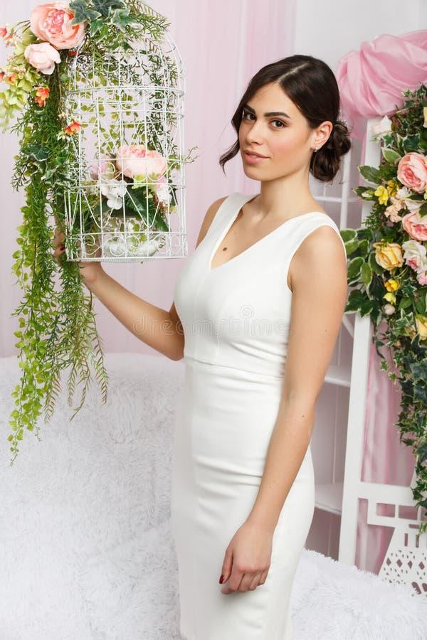 Εικόνα της όμορφης γυναίκας δίπλα στο κλουβί με τα λουλούδια στοκ εικόνες