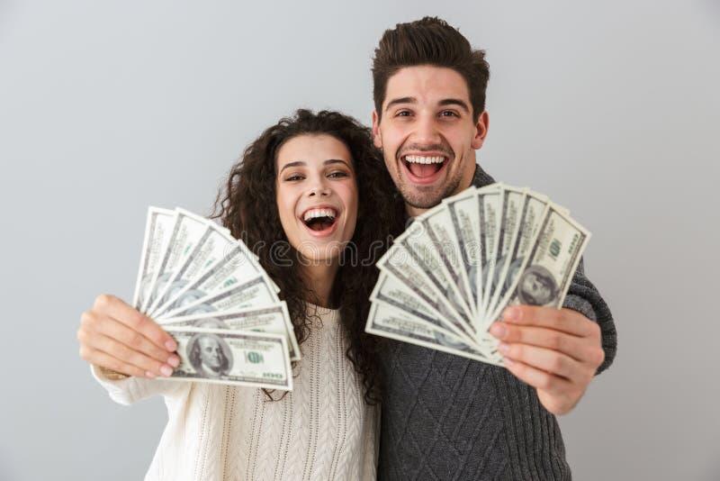 Εικόνα του ανεμιστήρα εκμετάλλευσης πλούσιων ανθρώπων και γυναικών των χρημάτων δολαρίων, που απομονώνεται πέρα από το γκρίζο υπό στοκ εικόνες