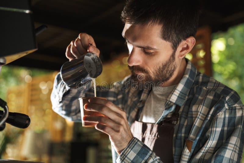 Εικόνα του αρσενικού ατόμου barista που κατασκευάζει τον καφέ εργαζόμενου στον καφέ ή το καφέ υπαίθριο στοκ φωτογραφίες