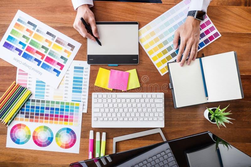 Εικόνα του αρσενικού δημιουργικού γραφικού σχεδιαστή που εργάζεται στην επιλογή χρώματος και που επισύρει την προσοχή στην ταμπλέ στοκ εικόνες