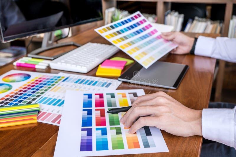 Εικόνα του αρσενικού δημιουργικού γραφικού σχεδιαστή που εργάζεται στην επιλογή χρώματος και που επισύρει την προσοχή στην ταμπλέ στοκ φωτογραφία με δικαίωμα ελεύθερης χρήσης