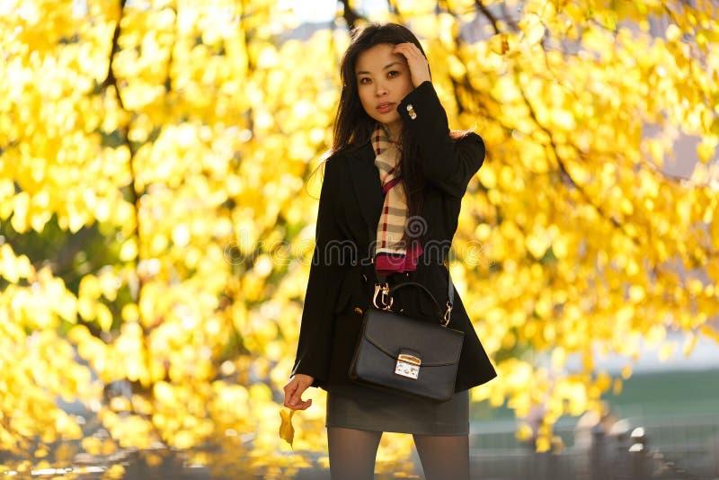 Εικόνα του ασιατικού κοριτσιού με το αλεύρι, στο μαύρο παλτό στο δάσος φθινοπώρου στοκ εικόνα με δικαίωμα ελεύθερης χρήσης