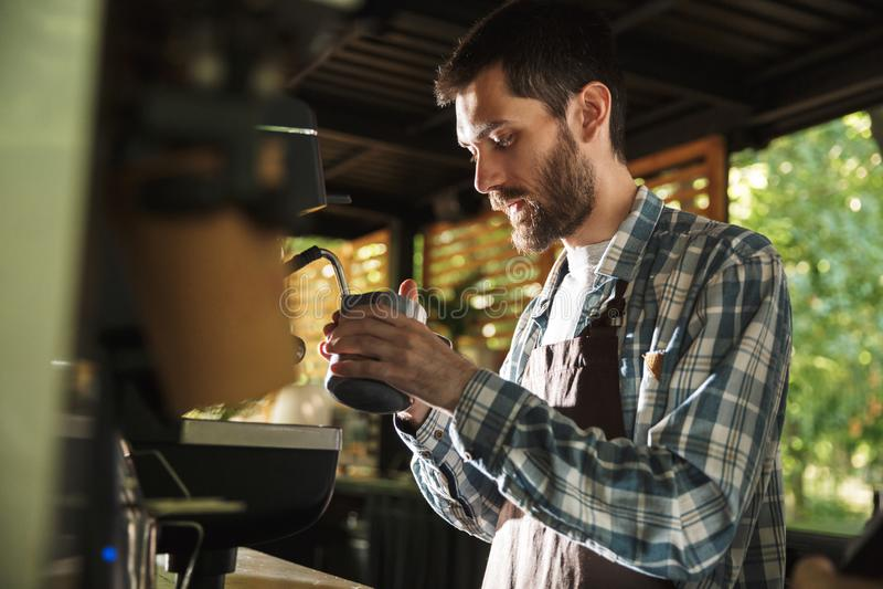 Εικόνα του ελκυστικού αγοριού barista που κατασκευάζει τον καφέ εργαζόμενου στον καφέ ή το καφέ υπαίθριο στοκ εικόνες