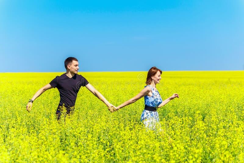 Εικόνα του ευτυχούς ζεύγους που τρέχει στο κίτρινο λιβάδι στοκ φωτογραφίες