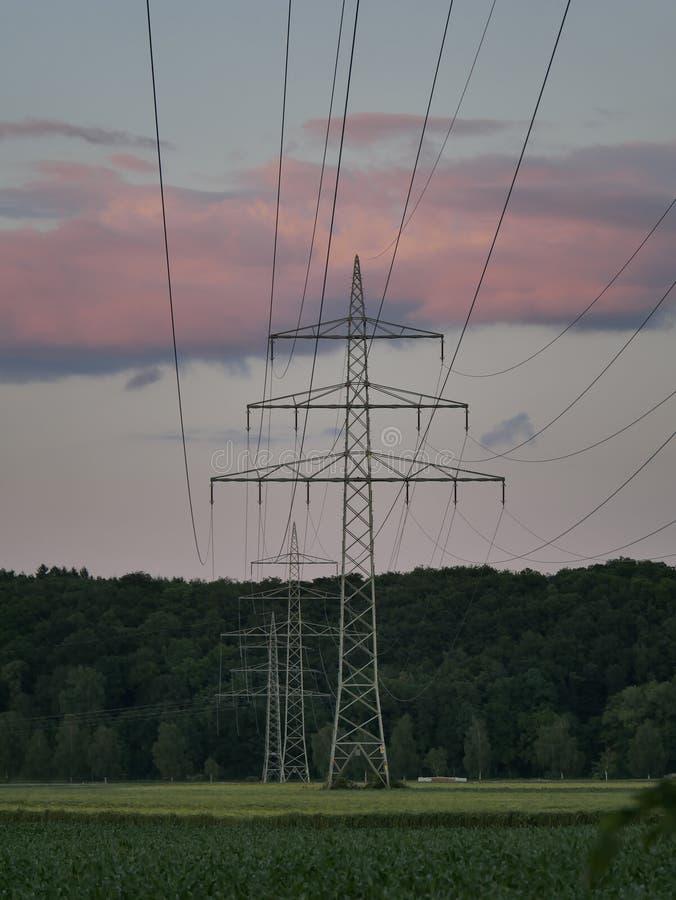 Εικόνα του ηλεκτροφόρου καλωδίου κατά τη διάρκεια του ηλιοβασιλέματος με τις εγκαταστάσεις παραγωγής ενέργειας στοκ εικόνες