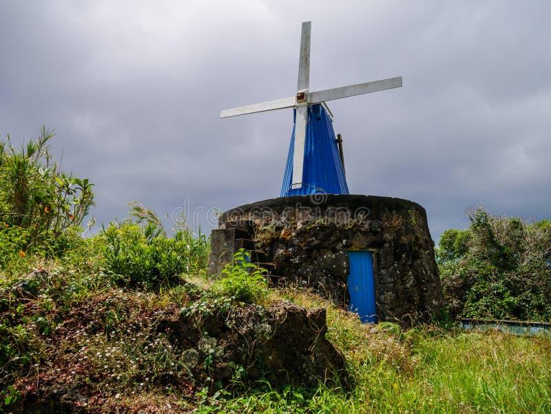 Εικόνα του μπλε ξύλινου ανεμόμυλου σε μια βάση πετρών στοκ φωτογραφία
