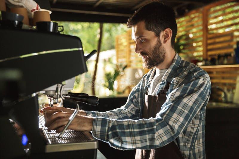 Εικόνα του νέου αγοριού barista που κατασκευάζει τον καφέ εργαζόμενου στον καφέ ή το καφέ υπαίθριο στοκ εικόνες
