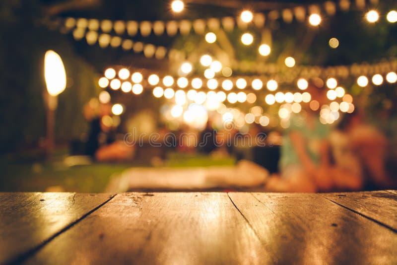 Εικόνα του ξύλινου πίνακα μπροστά από θολωμένο το περίληψη υπόβαθρο φω'των εστιατορίων στοκ εικόνες