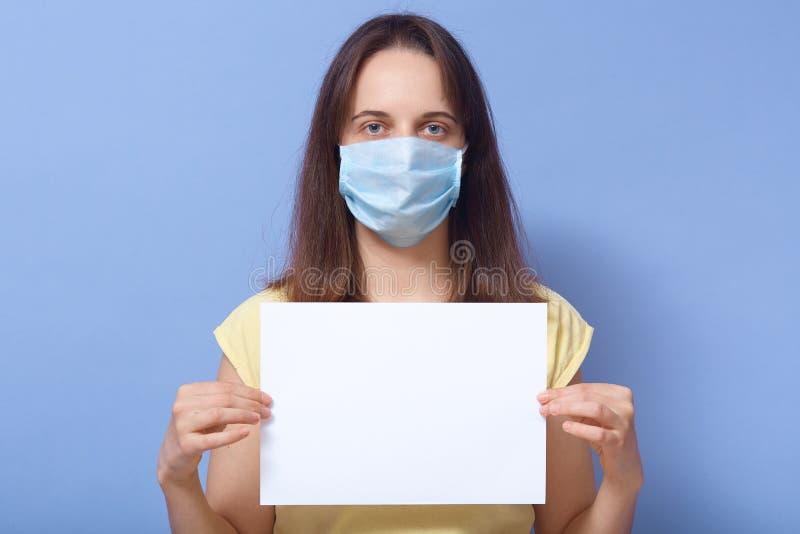 Εικόνα του στούντιο μιας σοβαρής προσεκτικής νεαρής γυναίκας που στέκεται απομονωμένη πάνω από το μπλε φόντο, κοιτάζοντας απευθεί στοκ φωτογραφίες
