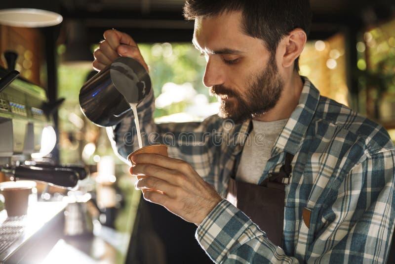 Εικόνα του σύγχρονου αγοριού barista που κατασκευάζει τον καφέ εργαζόμενου στον καφέ ή το καφέ υπαίθριο στοκ φωτογραφία