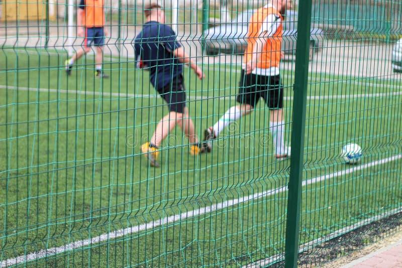 Εικόνα του τμηματικού πράσινου φράκτη Οι ποδοσφαιριστές με μια σφαίρα παίζουν στο υπόβαθρο στοκ φωτογραφίες με δικαίωμα ελεύθερης χρήσης