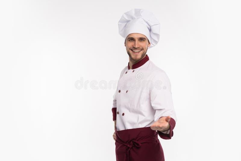 Εικόνα του χαμογελώντας νέου μάγειρα στην ομοιόμορφη στάση που απομονώνεται πέρα από το άσπρο υπόβαθρο Υπόδειξη καμερών στοκ φωτογραφία με δικαίωμα ελεύθερης χρήσης