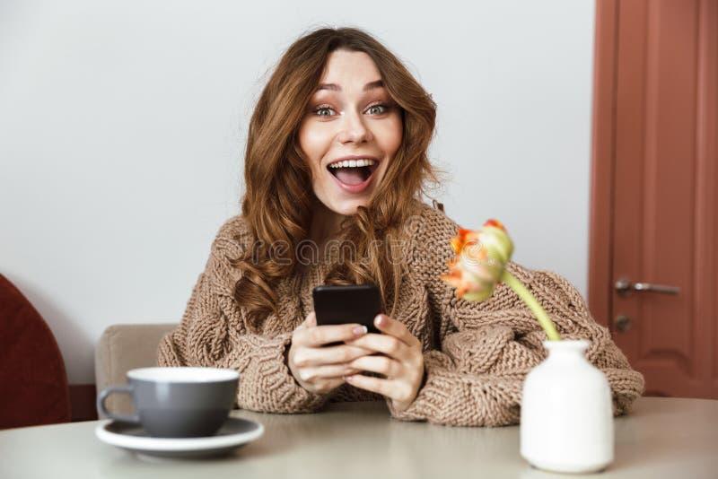 Εικόνα του χαρούμενου smartphone εκμετάλλευσης γυναικών brunette στα χέρια, whil στοκ εικόνα με δικαίωμα ελεύθερης χρήσης