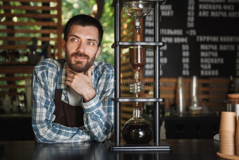 Εικόνα του χαρωπού αγοριού barista που κατασκευάζει τον καφέ εργαζόμενου στον καφέ ή το καφέ υπαίθριο στοκ φωτογραφία με δικαίωμα ελεύθερης χρήσης