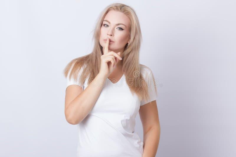 Εικόνα του όμορφου ξανθού δάχτυλου εκμετάλλευσης γυναικών κοντά στα χείλια της στοκ εικόνες